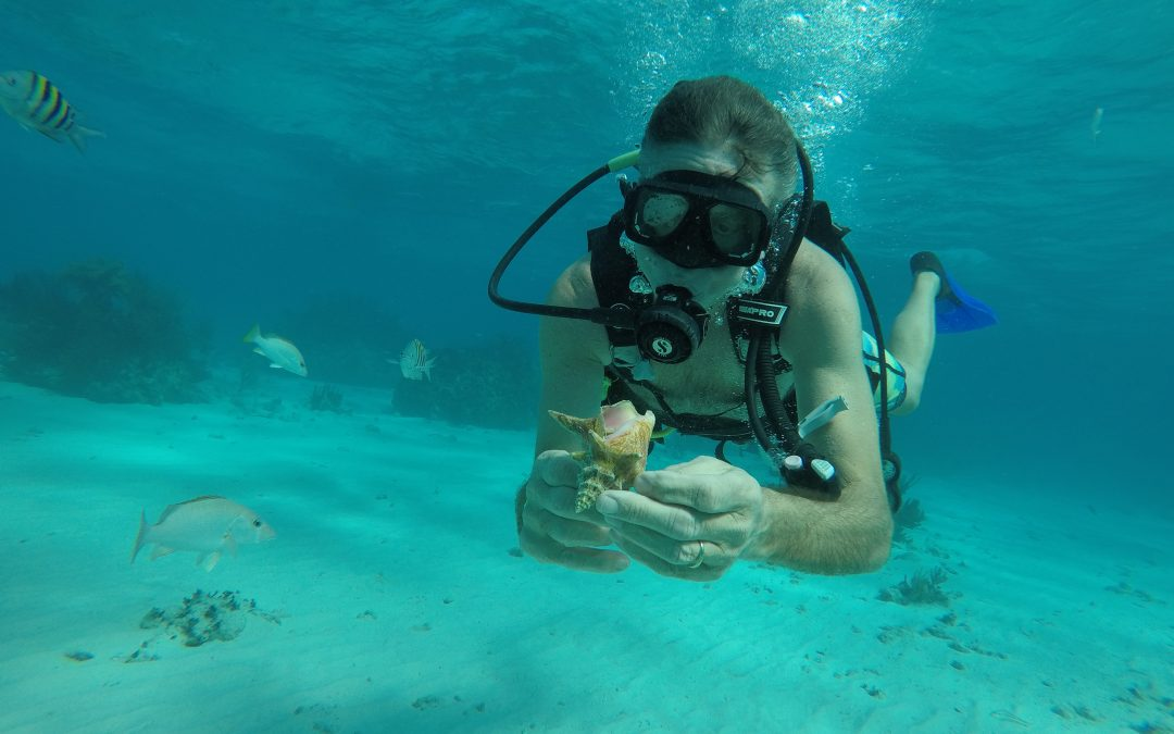 girl scuba diving holding a conch shell